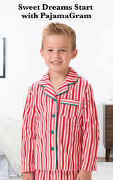 Boy wearing Candy Cane Fleece Boys Pajamas by bed with the following copy: Sweet Dreams Start with PajamaGram. image number 1