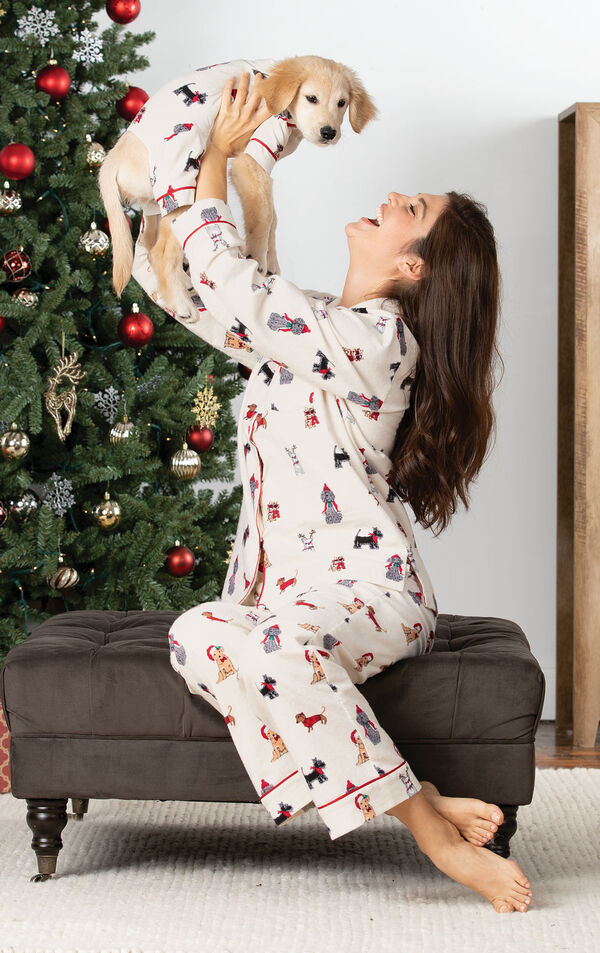 Woman wearing Christmas Dog Print Flannel Pajamas, holding up a puppy wearing matching pajamas by Christmas Tree image number 1