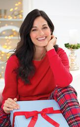 Model sitting down wearing Classic Red Stewart Plaid Thermal-Top Women's Pajamas holding a keepsake fabric gift box with a red bow image number 3