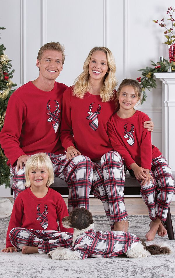Family sitting by Christmas Tree wearing matching Red and White Fireside Fleece Pajamas image number 4