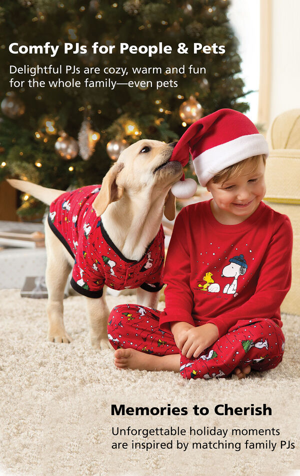 Boy and Dog wearing Snoopy and Woodstock Matching Pajamas with the following copy: Comfy PJs for People and Pets - Delightful PJs are cozy, warm and fun for the whole family - even pets. Memories to Cherish - Unforgettable holiday moments are inspired by matching family PJs. image number 2