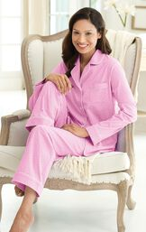 Model sitting in chair wearing pink button-up pajamas with white polka dots image number 2
