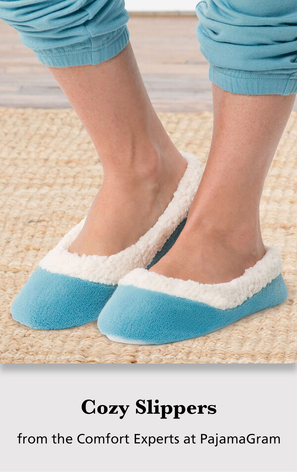 Model wearing Teal World's Softest Slippers standing on a rug with the following copy: Cozy Slippers from the Comfort Experts at PajamaGram image number 2