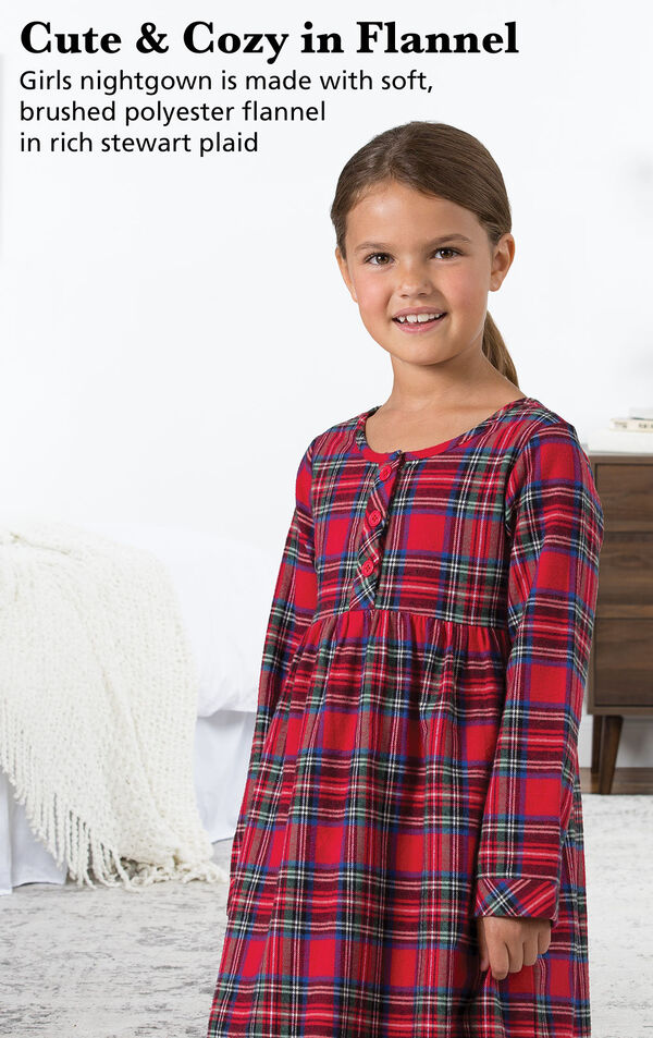 Girl wearing Stewart Plaid Flannel Girls Nighty next to bed with the following copy: Cute and Cozy in Flannel. Girls nightgown is made with soft, brushed polyester flannel in rich Stewart plaid. image number 2
