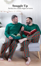 Couple sitting on the couch wearing matching Christmas Tree Plaid Pajamas with the following copy: Snuggle Up - Perfect for a Date Night at Home image number 1