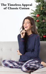 Model wearing Snowfall Plaid Thermal-Top Pajamas sitting on couch by Christmas Tree with the following copy: The Timeless Appeal of Classic Cotton image number 1