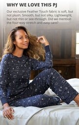 Model sitting on bed wearing Navy Blue Sun and Moon Print PJs for Women with the following copy: Our exclusive Feather Touch fabric is osft but not plush. Smooth but not silky. Lightweight but not thin or see-through. Four-way stretch and easy care. image number 2