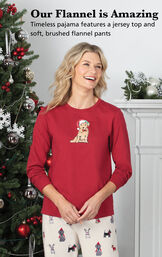 Model standing by Christmas tree wearing Red and Cream Christmas Dog Flannel Pajamas with the following copy: Timeless pajama features a jersey top and soft, brushed flannel pants image number 2
