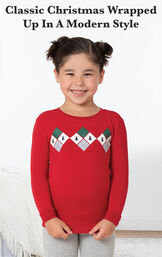 Model standing by bed wearing Red and Gray Holiday Argyle Girl's Pajamas with the following copy: Classic Christmas wrapped up in a modern style image number 2