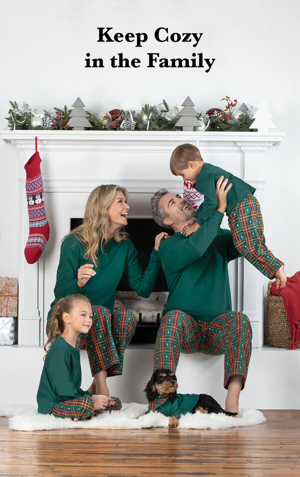 Family sitting by fireplace wearing matching Red and Green Christmas Tree Plaid Family Pajamas with the following copy: Keep Cozy in the Family image number 1