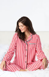 Model sitting on bed wearing Red and White Stripe Candy Cane Fleece Pajamas image number 1