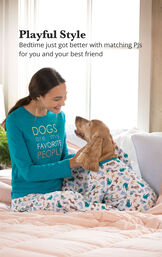 Woman and dog sitting on bed wearing matching Teal and Blue dog print pajamas with the following copy: Playful Style - Bedtime just got better with matching PJs for you and your best friend image number 1