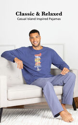 Model sitting on couch wearing Navy Margaritaville Easy Island Men's Pajamas with the following copy: Classic and Relaxed - Casual Island Inspired Pajamas image number 2