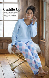 Model wearing Blue and Pink Snuggle Fleece Pajamas - Argyle  sitting with the following copy: Cuddle Up in our Exclusive Snuggle Fleece image number 2