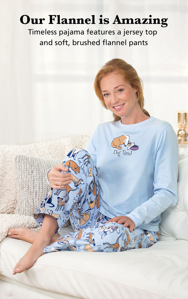 Model sitting on couch wearing Light Blue with Dog Print Dog Tired Jersey-Top Flannel Pajamas, with the following copy: Our Flannel is Amazing. Timeless pajama features a jersey top and soft, brushed flannel pants image number 1