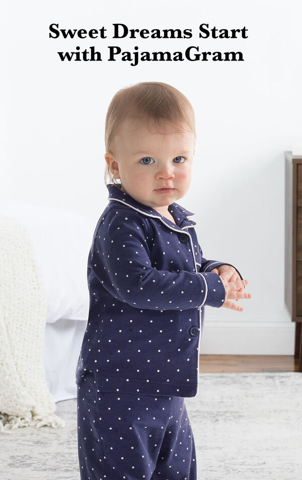 Infant wearing Classic Polka-Dot Infant Pajamas - Navy by bed with the following copy: Sweet Dreams Start with PajamaGram. image number 1
