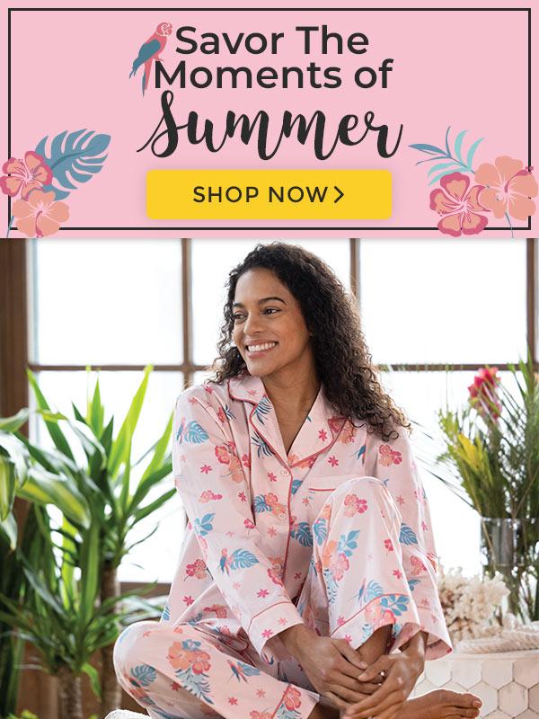 An image of a brunette woman wearing our PajamaGram Margaritaville pink hibiscus boyfriend pajamas